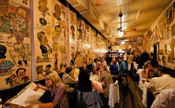 Which New York steak house, opened in 1926, features drawings of celebrities on its walls?